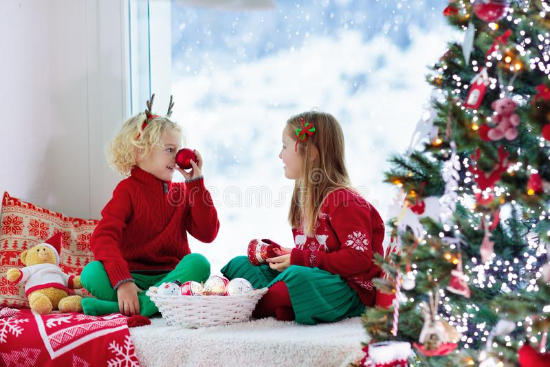 Kids decorate Christmas tree. Child on Xmas eve. Child decorating Christmas tree at home. Little boy and girl in knitted sweater with handmade Xmas ornament stock photography