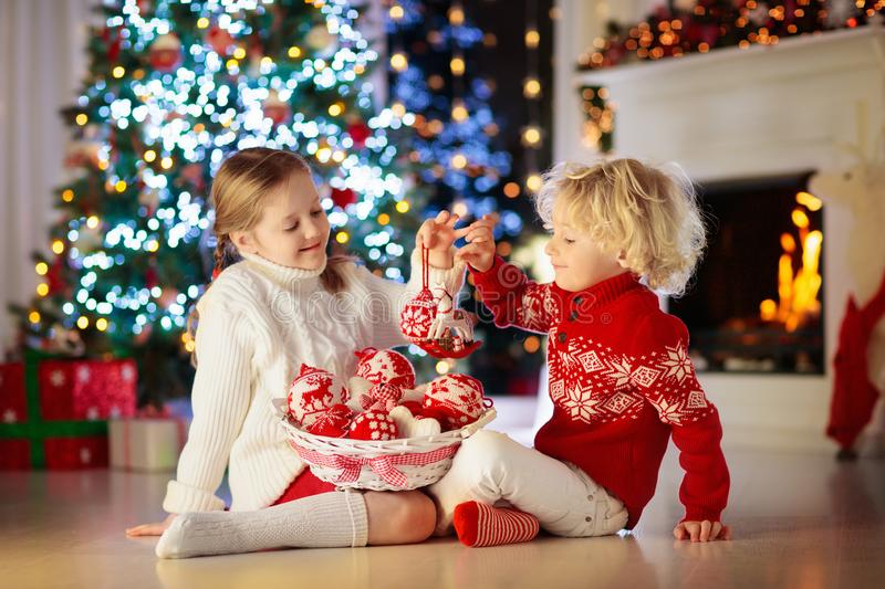 Child decorating Christmas tree at home. Little boy and girl in knitted sweater with handmade Xmas ornament. Family celebrating royalty free stock photos