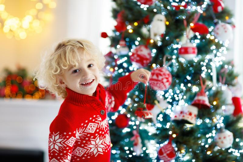 Child decorating Christmas tree at home. Little boy in knitted sweater with Xmas ornament. Family with kids celebrate winter. Holidays. Kids decorate living royalty free stock photo