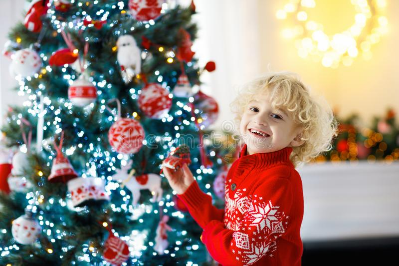 Child decorating Christmas tree. Kid on Xmas eve. Child decorating Christmas tree at home. Little boy in knitted sweater with Xmas ornament. Family with kids royalty free stock photos