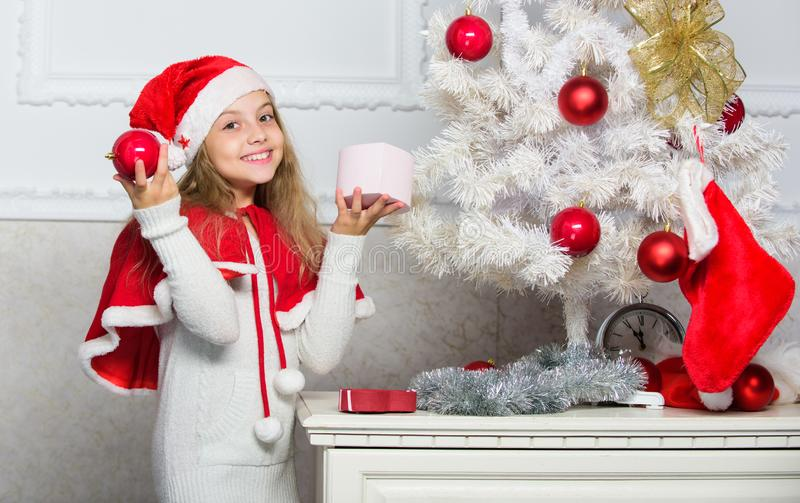 Child decorating christmas tree with red balls ornaments. Cherished holiday activity. Kid in santa hat decorating royalty free stock photo