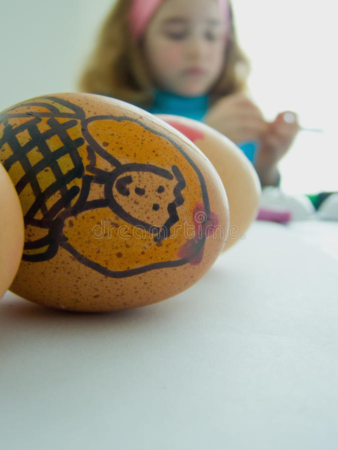 Child decorating Easter eggs stock images