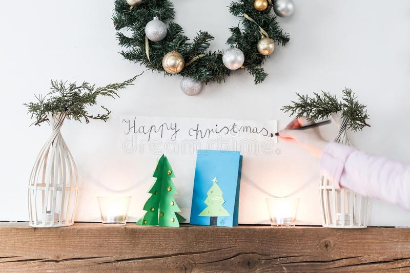 Child decorating fireplace with `Happy christmas` sign royalty free stock image