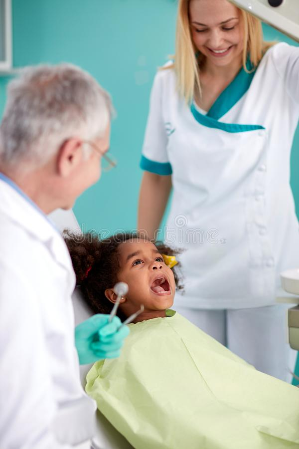 Child on dental check up. Cute black child on dental check up in chair stock photos