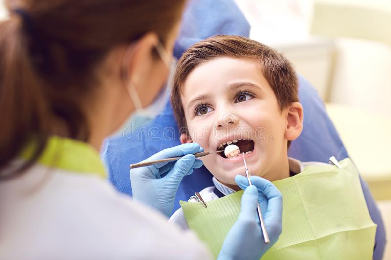 A child with a dentist in a dental office. Dental treatment in a children`s clinic royalty free stock image