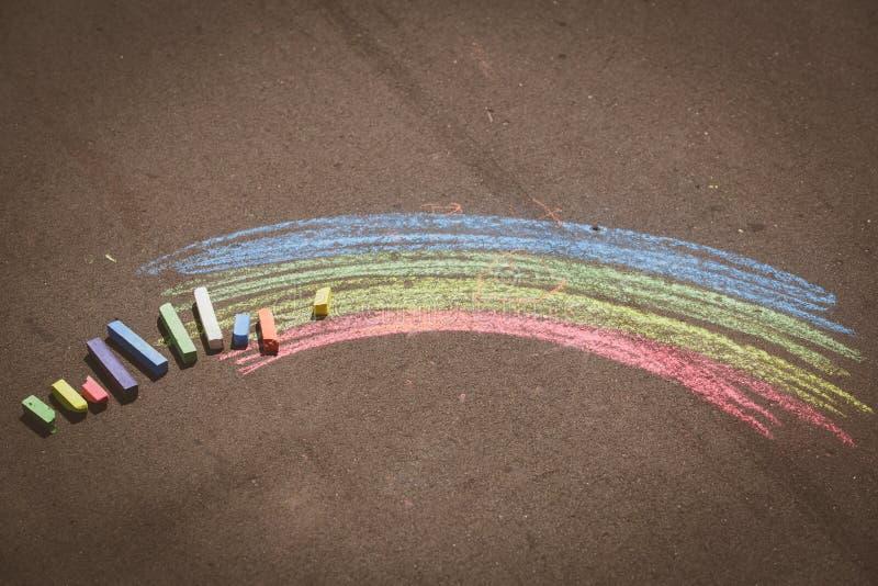 Child& x27; desenho de s do arco-íris e dos gizes em uma rua imagens de stock royalty free