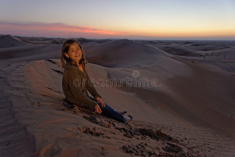 Child in desert at sunset royalty free stock image