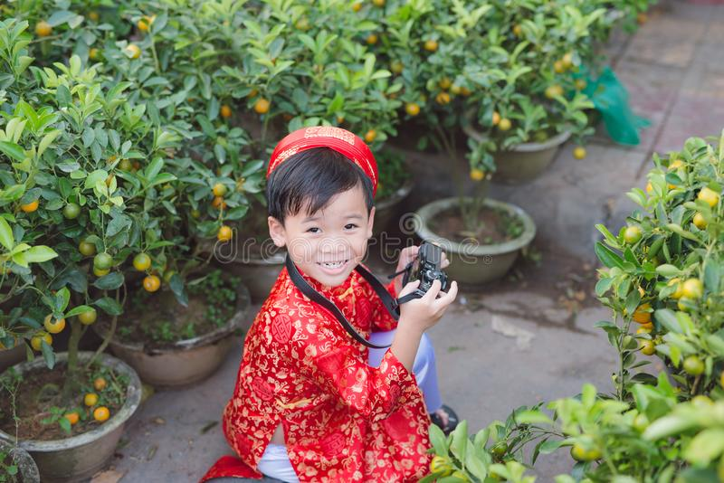Child with digital compact camera outdoors. Cute little Vietnamese boy in ao dai dress smiling. Tet holiday royalty free stock photos