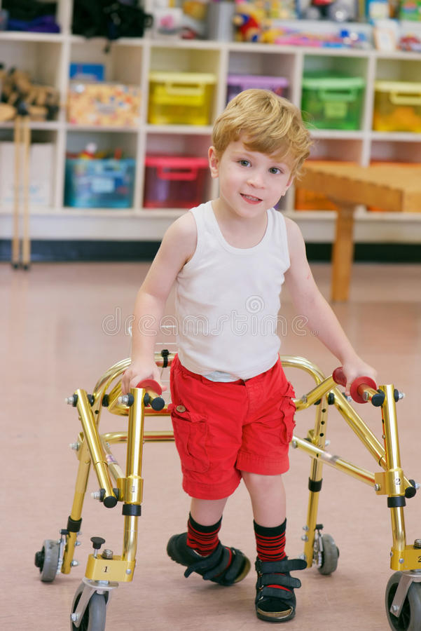 Child with disability. Happy Three years old boy with cerebral palsy walking with a walker in disability care centre royalty free stock photography