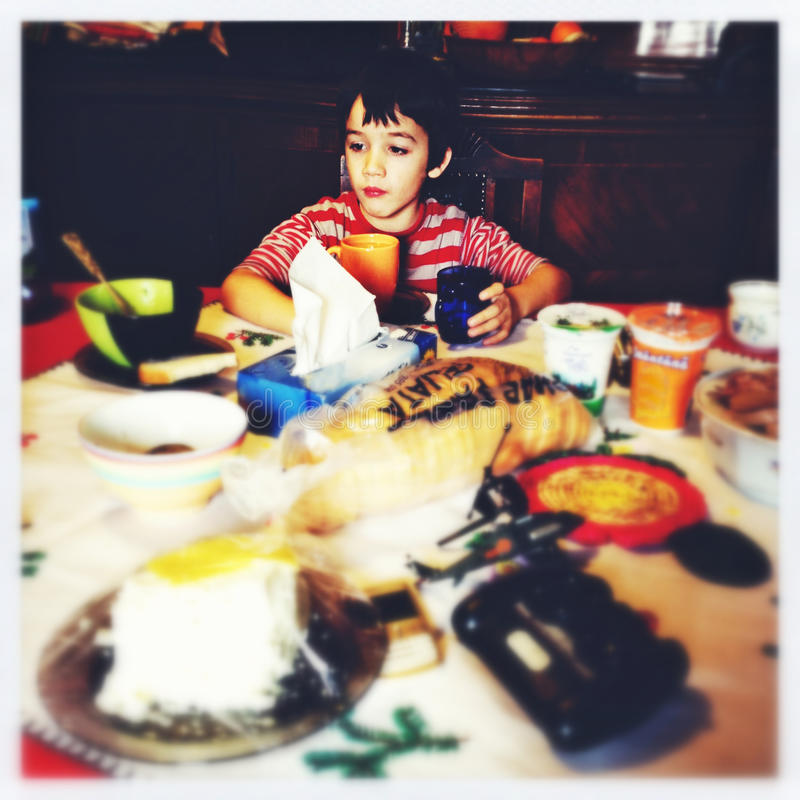 Child distracted while eating. Breakfast. Image taken with a mobile phone stock photo