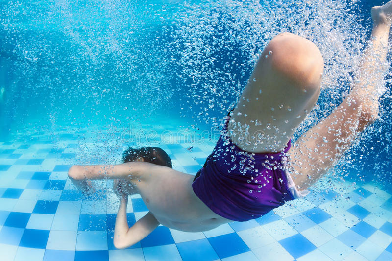 Child diving underwater in swimming pool royalty free stock image