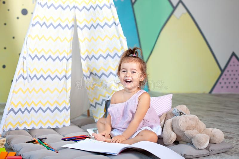Child does homework child draws in kindergarten. a preschooler learns to write and read. Creative kid. Little smiling girl draws w stock image