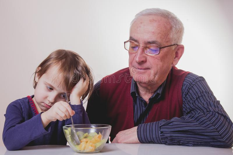 The child does not want to eat and has no appetite. Grandpa feeding his grandchild with fruits salad stock image