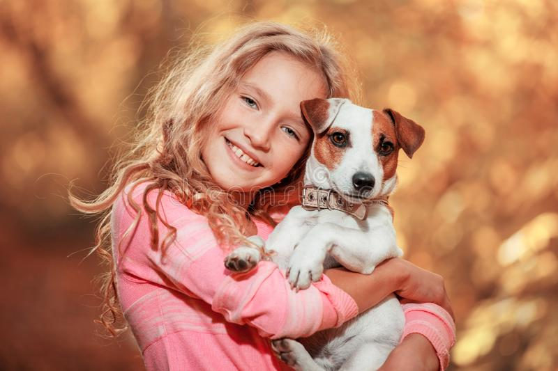 Child with dog at autumn. Happy girl with pet royalty free stock photography