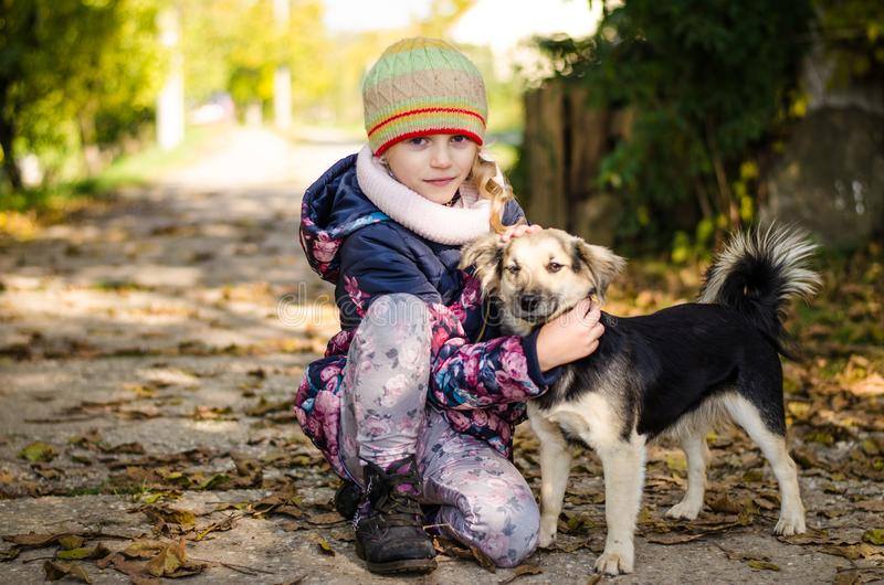 Child with dog in autumn time stock photo