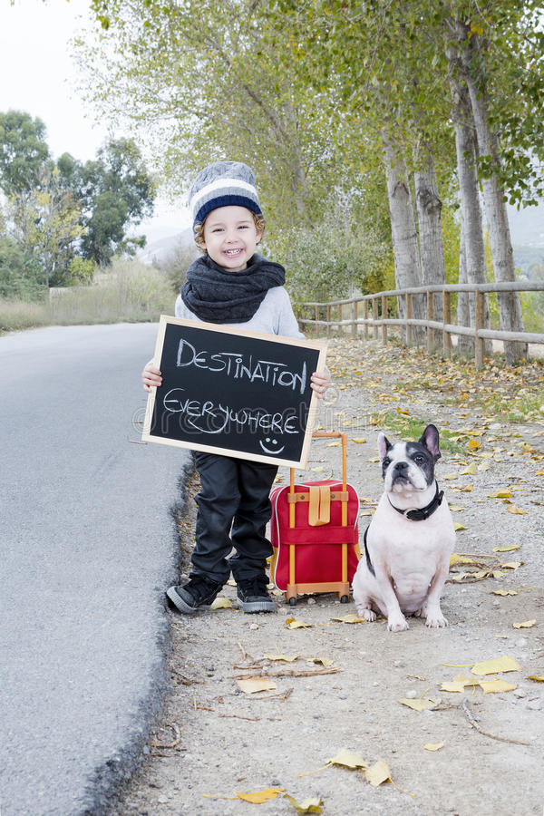 Child and dog hitchhiking. Smiling child holding a little blackboard with destination everywhere written with a white and black french bulldog and a suitcase stock photo