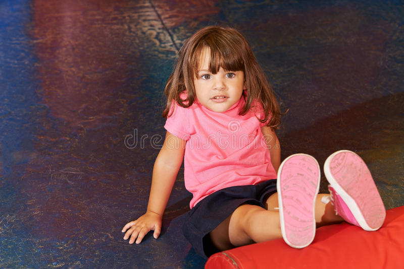 Child doing children sports in gym. Little child doing children sports in gym with her legs on a pillow stock images