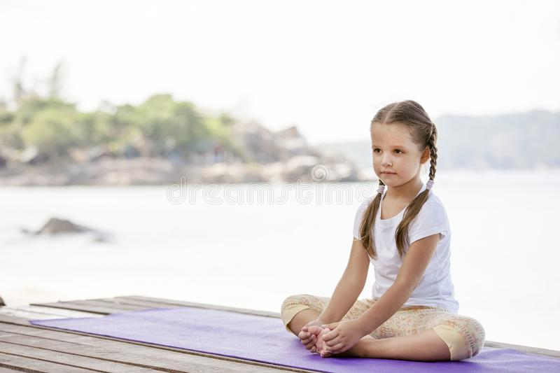 Child doing exercise on platform outdoors. Healthy lifestyle. Yoga girl stock images