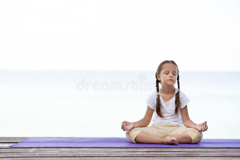Child doing exercise on platform outdoors. Healthy lifestyle. Yoga girl stock image