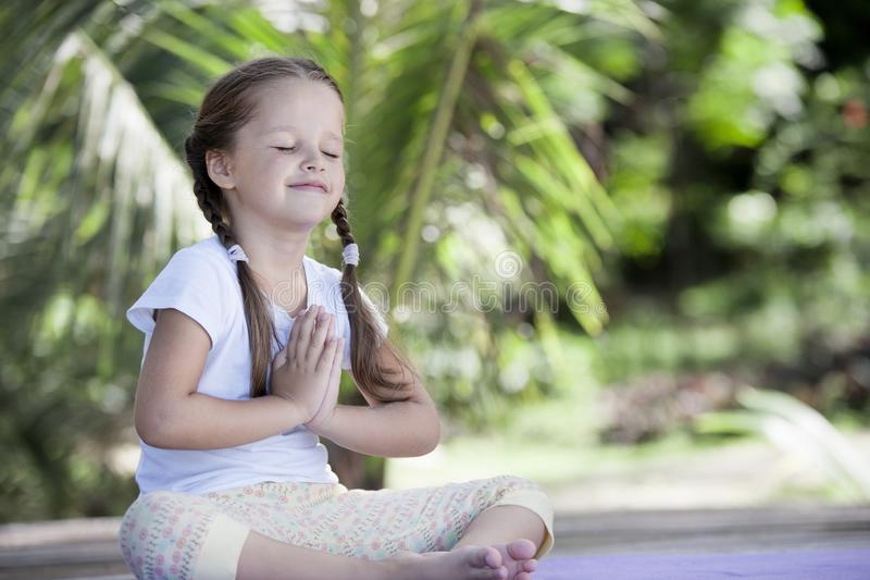 Child doing exercise on platform outdoors. Healthy lifestyle. Yoga girl stock photos