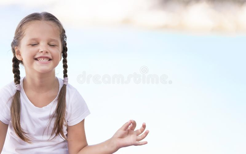 Child doing exercise on platform outdoors. Healthy lifestyle. Yoga girl stock photography
