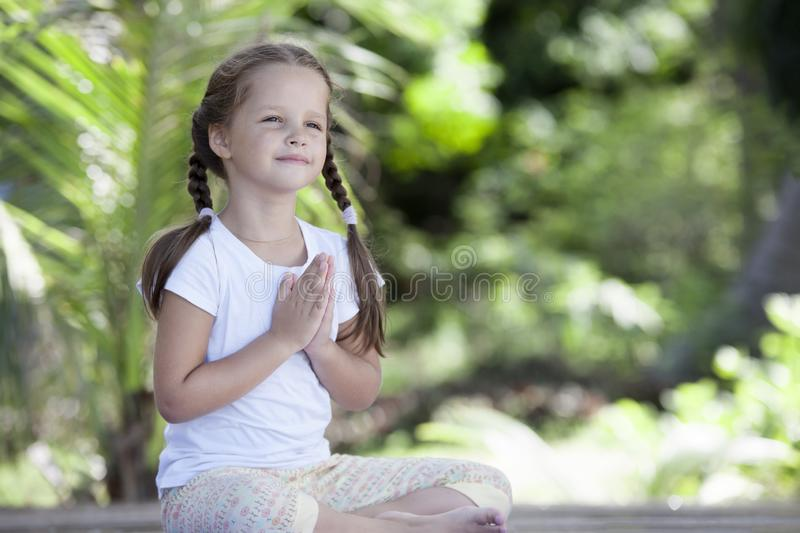 Child doing exercise on platform outdoors. Healthy lifestyle. Yoga girl royalty free stock photography