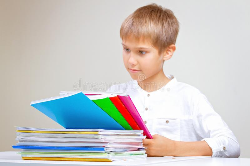 Child doing his homework at home. The boy sitting and looking in to books, notebooks and textbooks stock photography
