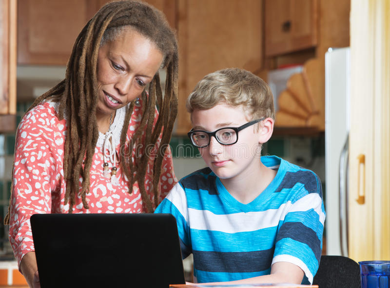 Child doing homework with foster parent in kitchen royalty free stock photos