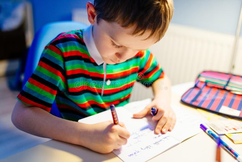 Child is doing homework in the light of the lamp stock image