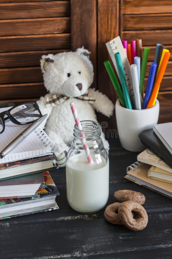 Child domestic work space and accessories for training and education - books, journals, notepads, notebooks, pens, pencils, tablet. And toy bear, bottle of milk stock photography
