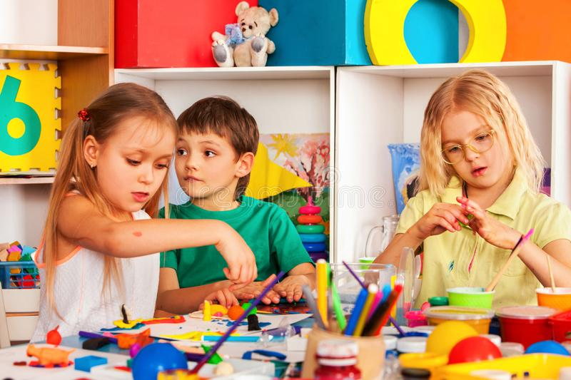 Child dough play in school. Plasticine for children. Plasticine mold in kindergarten. Kids knead modeling clay and choose playdough tools knife and stack in stock photo