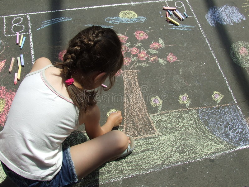 Child drawing on the asphalt w stock photos