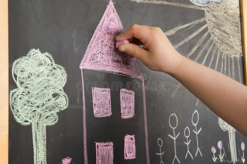 Child drawing on a blackboard. A child drawing a house on a blackboard royalty free stock photography