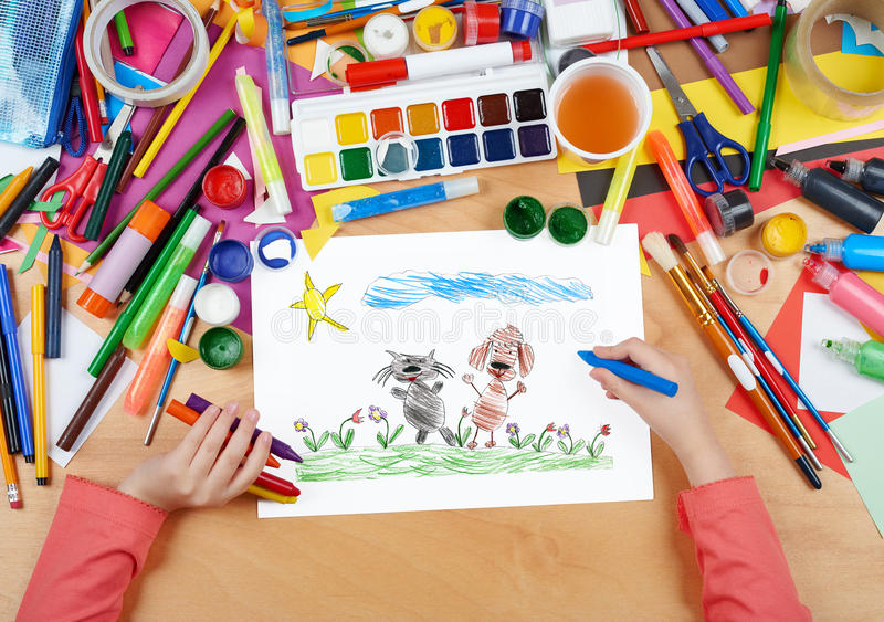 Child drawing cat and dog friends walk on grass, top view hands with pencil painting picture on paper, artwork workplace royalty free stock photos