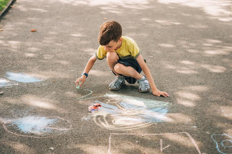 Child drawing with chalk outside in the park. On nice sunny day stock photography