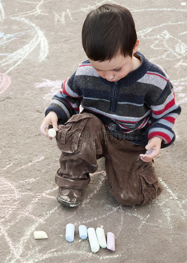 Child drawing with chalk stock photography