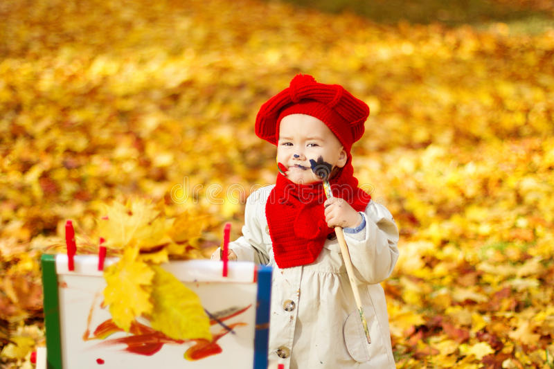 Child drawing on easel in Autumn Park. Creative kids development stock photos