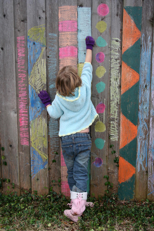 Child Drawing on Fence royalty free stock photos