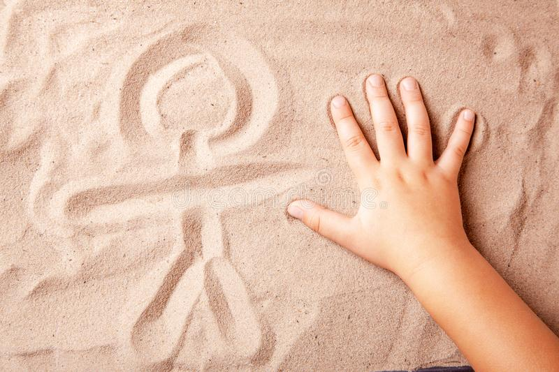 Child is drawing finger on the sand symbol of person stock images
