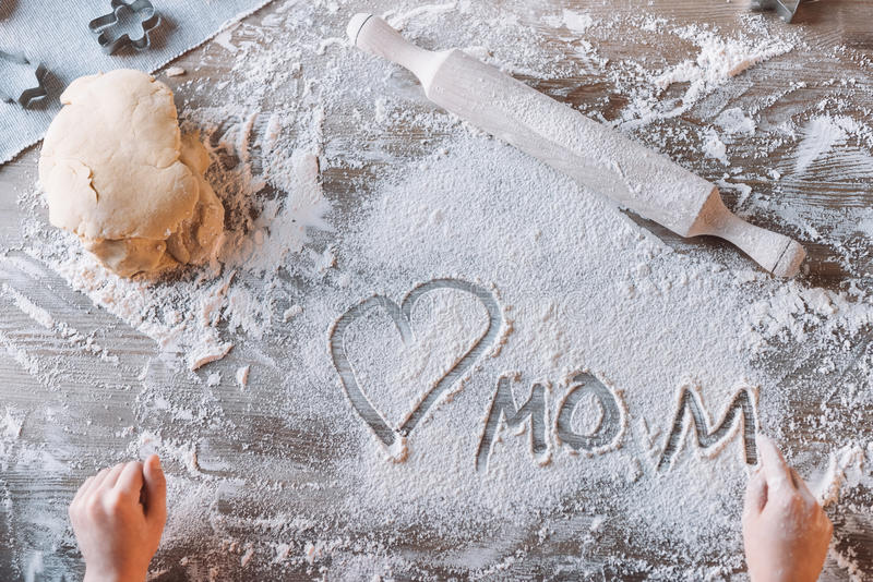 Child drawing heart symbol and word mom in flour on table, Mothers day concept royalty free stock photography
