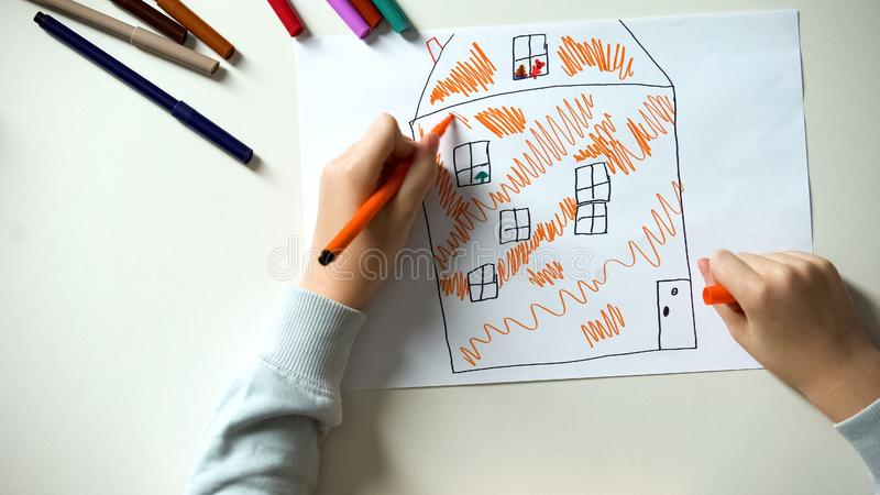 Child drawing house, orphan kid dreaming about parents and home, charity stock photos