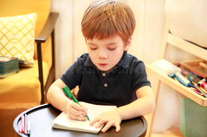 Child is drawing and painting with felt pen on paper of spiral notebook on small wooden table in living room at home. Childhood. stock photo