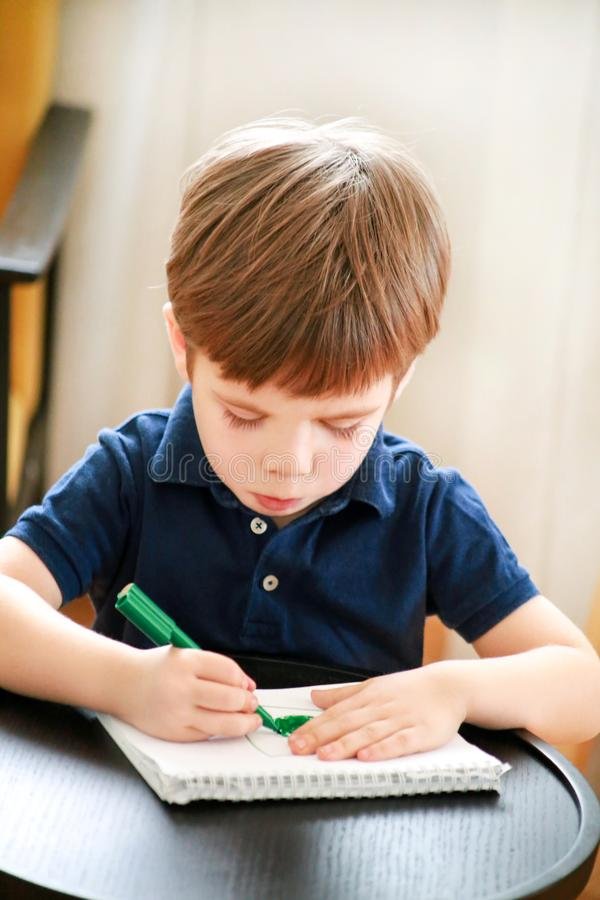 Child is drawing and painting with felt pen on paper of spiral notebook on small wooden table in living room at home. Childhood. royalty free stock photography