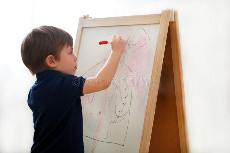 Child is drawing and painting with felt pen on paper of wooden drawing board artist easel for kids and children at home. Childhood stock photography
