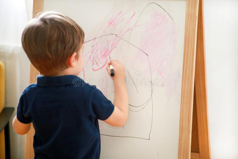 Child is drawing and painting with felt pen on paper of wooden drawing board artist easel for kids and children at home. Childhood royalty free stock photo