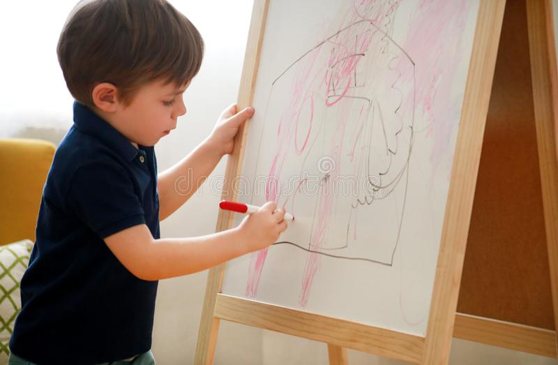 Child is drawing and painting with felt pen on paper of wooden drawing board artist easel for kids and children at home. Childhood stock photo
