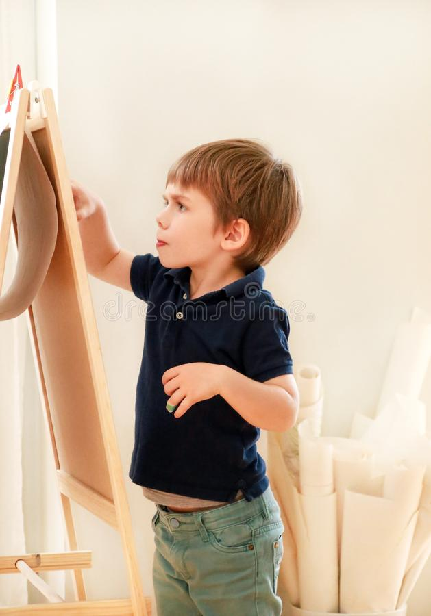 Child is drawing and painting with felt pen on paper of wooden drawing board artist easel for kids and children at home. Childhood royalty free stock image