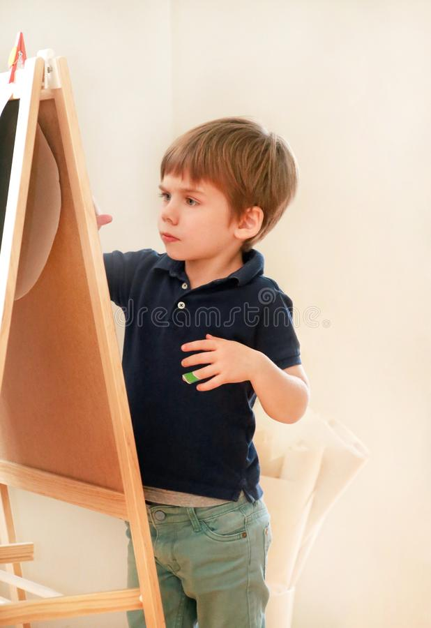 Child is drawing and painting with felt pen on paper of wooden drawing board artist easel for kids and children at home. Childhood royalty free stock images