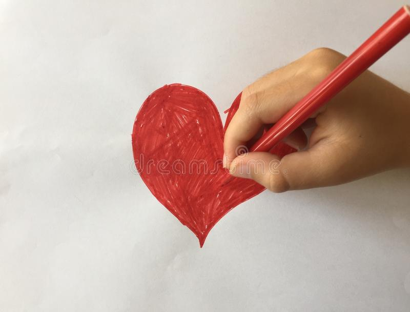 Child drawing a red heart. A child drawing a red heart stock photo