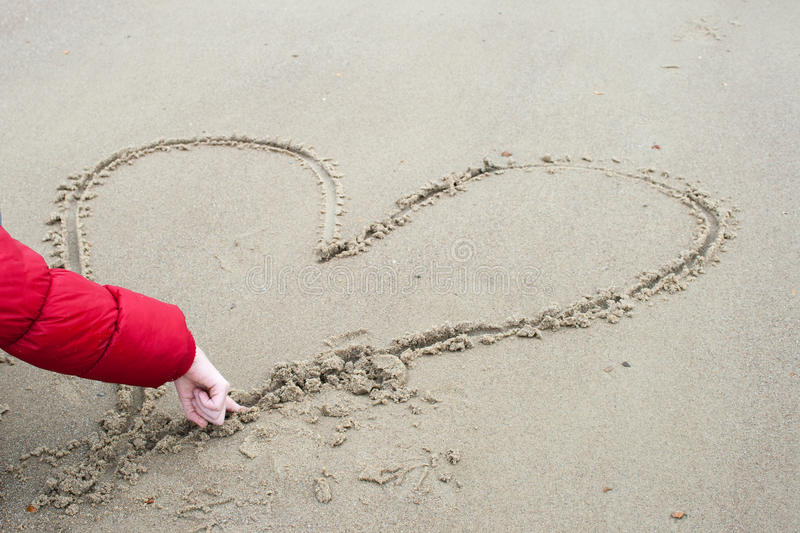 Child is drawing in the sand a heart. royalty free stock photos
